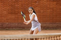 Портрет солнца волос брюнет шарика ракетки девушки суда тренировки девушки теннисиста подростка длинный учит зеленый зеленый цвет Стоковая Фотография RF