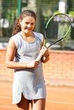 Портрет солнца волос брюнет шарика ракетки девушки суда тренировки девушки теннисиста подростка длинный учит зеленый зеленый цвет Стоковые Изображения