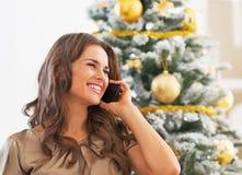Портрет сотового телефона женщины говоря около рождественской елки Стоковое Изображение RF