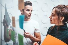 Портрет сотрудников стоя на размерах офиса за стеклянной стеной с липкими примечаниями стоковые фотографии rf