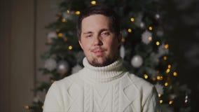 Портрет спокойного и довольного человека в теплом свитере который стоит перед рождественской елкой акции видеоматериалы