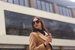 Портрет спокойной элегантной женщины поворачивая и рассматривая плечо, одетый черный свитер, бежевое пальто и стильные солнечные  стоковые изображения rf