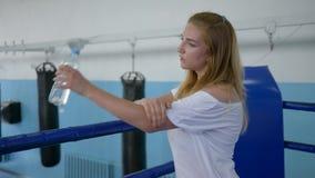 Портрет спортсменки выпивает воду от бутылки стоя на боксерском ринге отдыхая после трудной разминки в спортзале акции видеоматериалы