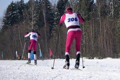 Портрет спортсмен-лыжника в шлеме и маске говоря на максимуме телефона в снеге вокруг стоковое фото