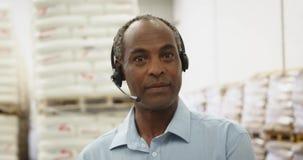Портрет среднего достигшего возраста человека в кладовае склада нося шлемофон 4k сток-видео
