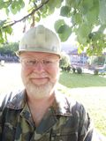 Портрет средн-постаретого человека с бородой против предпосылки зеленой травы Стоковые Фото
