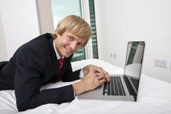 Портрет среднего взрослого бизнесмена используя компьтер-книжку в кровати дома стоковое изображение rf