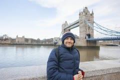 Портрет среднего взрослого человека в теплой одежде стоя перед мостом башни, Лондоном, Великобританией Стоковое Изображение