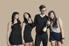 Портрет среднего взрослого человека и молодых женщин держа бутылку шампанского над покрашенной предпосылкой Стоковые Фотографии RF