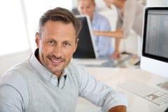 Портрет средн-постаретого человека работая с компьютером стоковая фотография