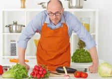 Портрет старого зрелого человека в рисберме подготавливая отрезать овощи Стоковое Изображение RF