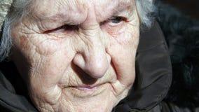 Портрет старой говоря женщины Серьезный сидеть бабушки внешний и говорить Конец-вверх Стоковое Изображение