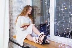 Портрет 10 старой лет книги чтения ребенка на окне на рождестве Стоковое Изображение