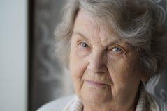 Портрет старой пожилой женщины постарел 80s внутри помещения Стоковая Фотография