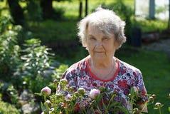 Портрет старой усмехаясь женщины в парке Стоковые Изображения