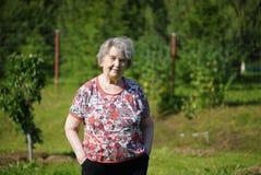 Портрет старой усмехаясь женщины в gargen Стоковая Фотография RF