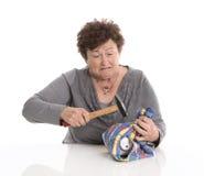 Портрет: старшая женщина ломая ее piggy коробку Изолировано над whi стоковые фото