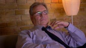 Портрет старшего бизнесмена в каналах костюма переключая по телевизору отпускает вверх связь после трудного рабочего дня видеоматериал