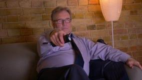 Портрет старшего бизнесмена в костюме ослабляя перед ТВ после того как трудный рабочий день отпустит вверх связь акции видеоматериалы