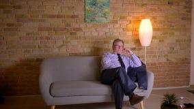 Портрет старшего бизнесмена в костюме сидит вниз на софе и переключателях на ТВ после трудного рабочего дня видеоматериал