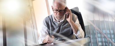 Портрет старшего бизнесмена говоря на мобильном телефоне, трудном lig стоковая фотография