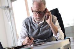 Портрет старшего бизнесмена говоря на мобильном телефоне, трудном свете Стоковое фото RF