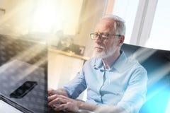 Портрет старшего бизнесмена работая на компьтер-книжке, световом эффекте Стоковое Фото