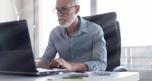 Портрет старшего бизнесмена работая на компьтер-книжке, световом эффекте Стоковое фото RF