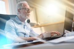 Портрет старшего бизнесмена работая на компьтер-книжке, световом эффекте Стоковая Фотография