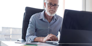 Портрет старшего бизнесмена работая на компьтер-книжке, трудном свете Стоковое Изображение RF