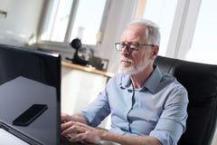 Портрет старшего бизнесмена работая на компьтер-книжке, трудном свете Стоковое Фото