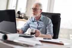 Портрет старшего бизнесмена работая на компьтер-книжке, трудном свете Стоковая Фотография RF