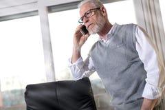 Портрет старшего бизнесмена стоя и говоря на мобильном телефоне Стоковые Изображения