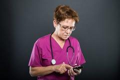 Портрет старшего доктора дамы просматривая на smartphone стоковое изображение