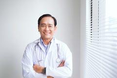 Портрет старшего доктора стоя в медицинском офисе Стоковое фото RF