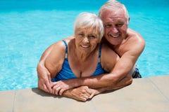 Портрет старшего одина другого обнимать пар в бассейне Стоковые Изображения
