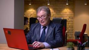 Портрет старшего человека в стеклах в официальном костюме печатая на ноутбуке находясь в замешательстве в офисе видеоматериал