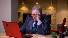 Портрет старшего человека в стеклах в официальном костюме работая с ноутбуком будучи смущанным в офисе сток-видео