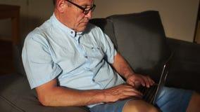 Портрет старшего человека работая при компьтер-книжка сидя дома в стуле, смотря экран компьютера акции видеоматериалы