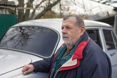 Портрет старшего человека стоя около его старого автомобиля стоковое фото