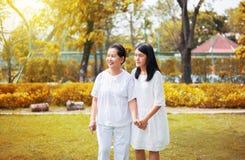 Портрет старшей азиатской женщины с молодыми женщинами идя на парк совместно в вечер, счастливый и усмехаться стоковое изображение rf