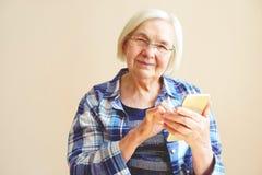 Портрет старшей женщины используя мобильный телефон дома Стоковая Фотография