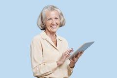 Портрет старшей женщины используя ПК таблетки против голубой предпосылки Стоковое Фото