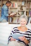 Портрет старшей женщины используя таблетку пока сидящ на софе Стоковые Фото