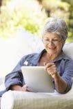 Портрет старшей женщины используя таблетку цифров дома Стоковые Фотографии RF
