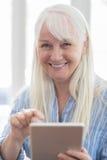 Портрет старшей женщины используя таблетку цифров дома Стоковые Изображения