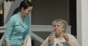 Портрет старшей женщины принимая медсестру таблеток дает медицину усмехаясь совместно на Outdoors дома престарелых на съемке солн сток-видео