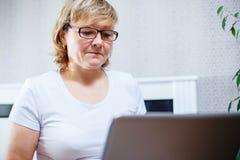 Портрет старшей женщины работая на компьтер-книжке Стоковая Фотография RF