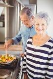Портрет старшей женщины стоя при супруг варя еду в предпосылке Стоковые Фотографии RF