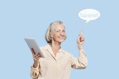 Портрет старшей женщины с ПК таблетки указывая на пузырь чириканья против голубой предпосылки Стоковые Фото